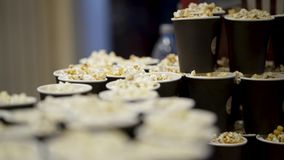 Många koppar av popcorn i bio actinium Läckert doftande nytt popcorn som lagas mat för film i bio Afton in arkivfilmer