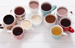 Många koppar av varma drinkar ooden på tabellen Royaltyfria Bilder