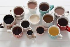 Många koppar av varma drinkar på trätabellen Arkivfoto