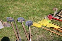 Många krattar, skyfflar, och borstar för att göra ren territoriet ligger på gräsplanen royaltyfria bilder