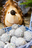 Många kulör jul klumpa ihop sig i en korg och under bakgrunden för xmas för trädigelkotten den färgrika Fotografering för Bildbyråer