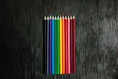 Många kulöra blyertspennor på en svart bakgrund nya blyertspennor Arkivfoton