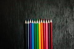 Många kulöra blyertspennor på en svart bakgrund nya blyertspennor Arkivbild