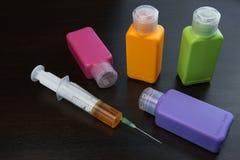 Många kulöra flaskor med flytande och injektionssprutan på svart bakgrund Arkivfoton