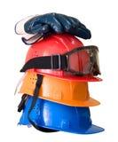 Många kulöra hardhats, handskar och goggles arkivfoton