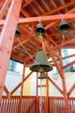 Många kyrkliga klockor i gammal byggnad inom den Zaraysk Kremlväggen i stad Hänga ner från röda trästrålar på Royaltyfria Foton