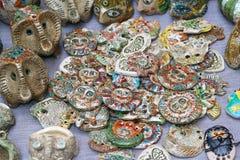 Många lerastatyetter av olika former och olika färger som ligger på tabellen arkivfoto