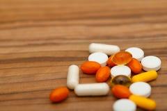 Många ljusa medicinpiller på träbakgrund arkivfoton