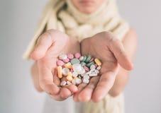 Många mång--färgade preventivpillerar i händer för en kvinna på vit bakgrund Royaltyfri Foto