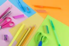 Många mång--färgade skolatillförsel inklusive saxblyertspennor och radergummin på enfärgad bakgrund arkivbilder