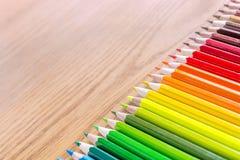 Många mångfärgade blyertspennor på en träbakgrund Olika kulöra blyertspennor med utrymme för text Royaltyfri Fotografi