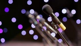 Många mikrofoner på etapp i strålarna av att blinka tänder stock video