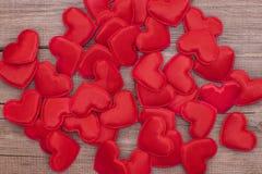Många mjuka röda hjärtor spridde på ett träbräde Royaltyfria Foton