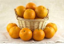 Många mogna apelsiner i brun vide- korg och near isolerade det Fotografering för Bildbyråer