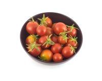 Många mogna tomater i lilor bowlar den isolerade closeupen Arkivbild