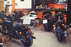 Många motorcyklar på golvet med seminariumhjälpmedel, ett modernt garage, lagring och reparation Denna cykel ska vara perfekt rep Arkivbild