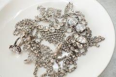Många mousserande smycken på en vit platta begreppet av lyxigt liv, rikedom, glamour, mode och bröllop royaltyfria foton