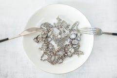 Många mousserande smycken på en vit platta med en kniv och en gaffel Begreppet av lyxigt liv, rikedom, glamour, mode och royaltyfri fotografi