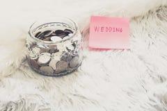 Många mynt i en pengarkrus med bröllopetiketten på kruset royaltyfria foton
