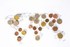Många mynt på världskarta royaltyfria bilder