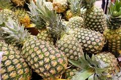 Många nya härliga ananors i en hög i lagret royaltyfri bild