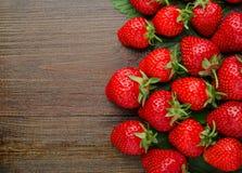 Många nya jordgubbar på gammal träbakgrund Fotografering för Bildbyråer
