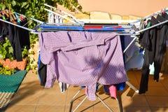många olik kläder som rymmer i tvättande linje på en trädgård i en solig dag arkivfoton