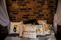 Många olika dekorativa kuddar på väggen för sängbaldakintegelsten arkivbilder