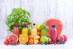 Många olika frukter och bär och fruktsafter i plast- flaskor Vattenmelon banan, applcsin, blåbär, jordgubbar, basilika på royaltyfri foto