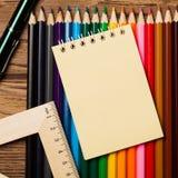 Många olika kulöra blyertspennor och tom anteckningsbok på trätabellen Royaltyfri Fotografi