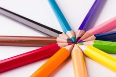 Många olika kulöra blyertspennor på vit bakgrund Fotografering för Bildbyråer