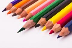 Många olika kulöra blyertspennor på vit bakgrund Royaltyfria Bilder