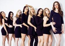 Många olika kvinnor i linje, bärande utsmyckade små svarta klänningar, Arkivfoton
