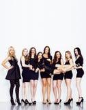Många olika kvinnor i linje, bärande utsmyckade små svarta klänningar, Arkivfoto