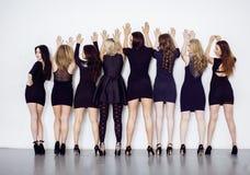 Många olika kvinnor i linje, bärande utsmyckade små svartklänningar, festar makeup, sedlighetsrotelbegrepp Royaltyfria Foton