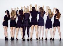 Många olika kvinnor i linje, bärande utsmyckade små svartklänningar, festar makeup, sedlighetsrotelbegrepp Royaltyfria Bilder