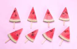 Många olika ljusa mogna skivor av vattenmelon på en pinne på en ljus rosa bakgrund Arkivfoto