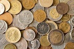 Många olika mynt på tabellen Bakgrund av mynt arkivfoton
