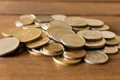 Många olika mynt på tabellen Begreppet av armod royaltyfria foton