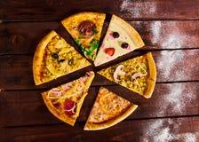 Många olika sorter av pizza på tabellen arkivbilder