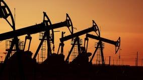 Många olje- pumpar på solnedgången under den röda himlen på industriellt plattformfält med hydrauliska extraktionenheter för rå o