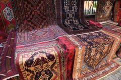 Många orientaliska mattor med geometriska till salu färger och designer Arkivbilder