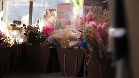 Många pappers- påsar av blommor i blomsterhandeln är klart till salu stock video