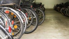 Många parkerade cyklar i ett garage Arkivbilder