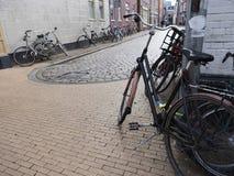 Många parkerade cyklar i mitten av den gamla holländska staden groningen Royaltyfria Bilder