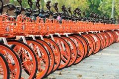 Många parkerades den orange cykeln för hyra arkivfoto