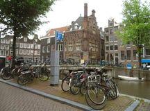 Många parkeringscyklar och holländsk traditionell arkitektur längs kanalen i Amsterdam arkivbilder