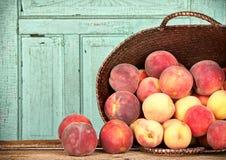 Många persikor i korg arkivfoton