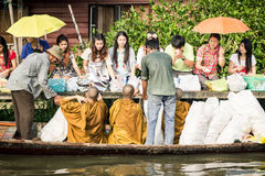 Många personer ger allmosa till munkar i Ladkrabang, Bangkok, Thailand Royaltyfria Bilder