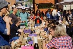 Många personer som dricker öl och äter mat under utomhus- gatamatfestival Arkivbilder